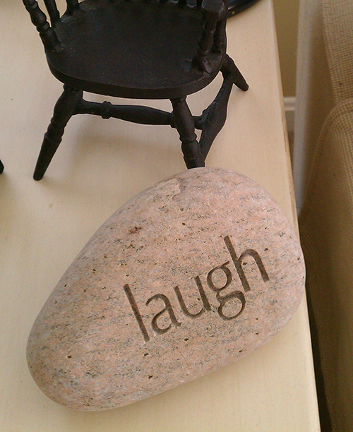 rock with word laugh etched into it