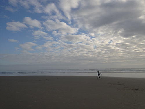 Photo of tiny lady skipping on sand at beach