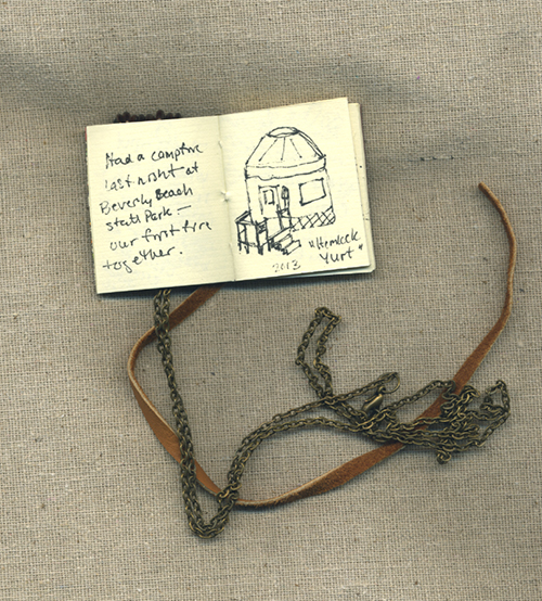 Photo of small book necklace with sketch of yurt