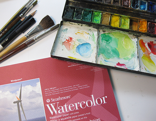 photo of watercolor sketchbook and dried watercolors with brushes