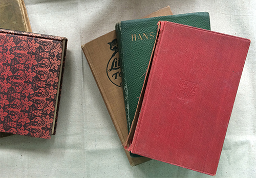 photo of vintage and weathered hardcover cloth bound books