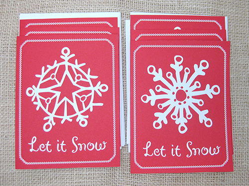 Let it Snow christmas card featuring 2 white snowflake designs on red background