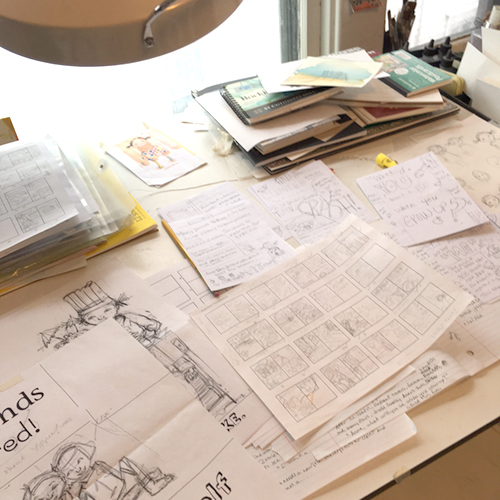 Abby Dening's drawing table covered with sketches and text for her picture book