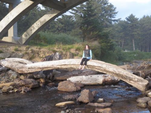 Abby sitting on natural log bridge