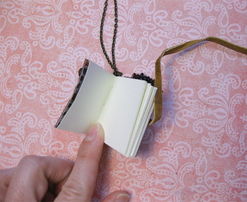 photo showing open blank pages of small book necklace