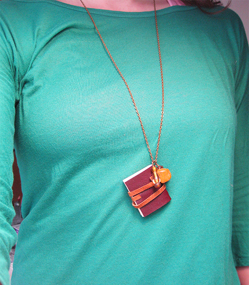 lady wearing small handmade book on a metal chain