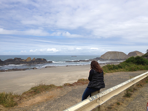Abby sketching on side of the road looking at ocean