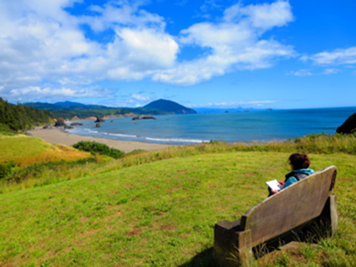 Photo of girl sitting on bench on cliff overlooking Portland coastline