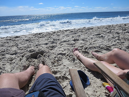 photo of man and lady's legs in the sand