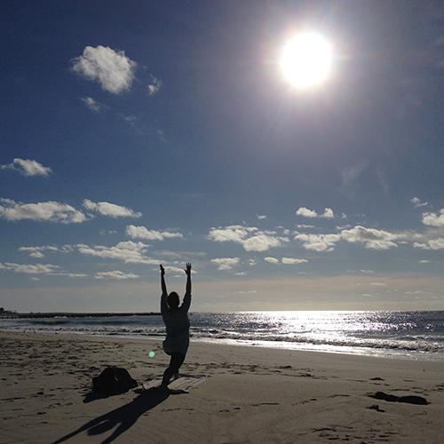abby in warrior 1 pose on beach