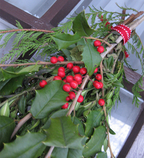 photo of holly and evergreens on door