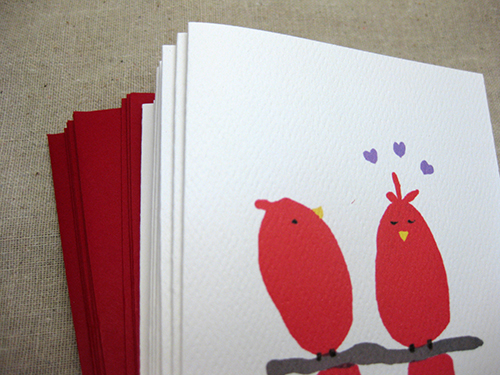 2 red birds painted on a valentine card