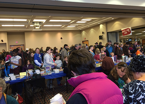 photo of room filled with adults and children at the author and illustrator signing room