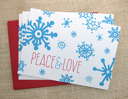 holiday card with blue snowflakes and thin red type saying peace & love